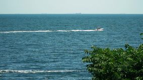 Motor boat floating in the sea. View from the shore stock footage