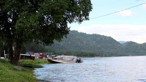 Motor boat moored at the lake shore. Motor boats moored to the shore near the tree in the summer stock footage