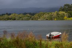 Motor boat near river bank with forest on the other side. Red and white boat on lake before thunderstorm. Storm sky with deep blue clouds over river with boat stock images