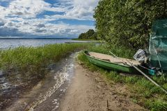 The motor boat is ready to enter the waves of the lake for fishing. A large lake with clear water and beautiful vegetation surprises our imagination, the lake Stock Photography