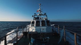 Motor boat with russian flag fast going over ocean water under clear sky. On sunny windy day, nose view stock footage