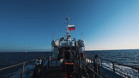 Motor boat with russian flag fast going over sea water under clear sky. On sunny windy day, stern view stock video