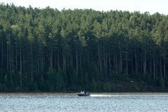 Motor boat is sailing along a blue river. Stock Photos