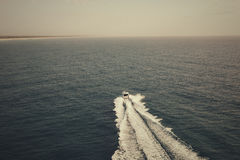 Motor boat sailing towards the horizon Royalty Free Stock Image
