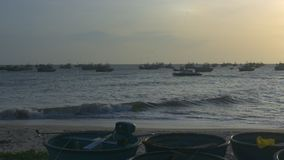 Motor Boat Sails along Bay and Round Fishing Boats. Camera shows motor boat sailing along ocean bay and round fishing boats on foreground against sunset stock footage