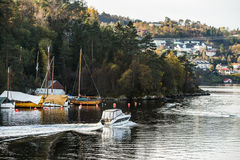 A motor boat sails along the fjord Stock Photos