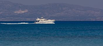 Motor boat sails past in the distance , Crete Greece stock image