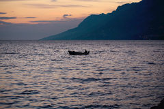 Motor boat in sea. Motor boat floats in blue sea water along mountain coast after sunset over evening sky Royalty Free Stock Photo
