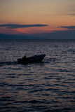 Motor boat in sea. Motor boat floats in blue sea water along mountain coast after sunset over evening sky Stock Photography
