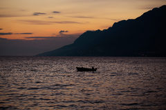 Motor boat in sea. Motor boat floats in blue sea water along mountain coast after sunset over evening sky Stock Photos
