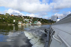 Motor boat and a small village on the Volga river Stock Images