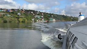 Motor boat and a small village on the Volga river stock video
