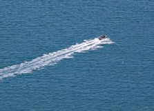 A motor boat speeds across the turquoise sea that surrounds Mount Maunganui in North Island, New Zealand royalty free stock image