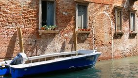 Motor boat stands on a Venetian canal under a beautiful vintage brick wall and windows with flowers in pots on the. A motor boat stands on a Venetian canal under stock footage