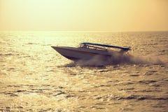 Motor boat on sunset. Vintage toned image royalty free stock image