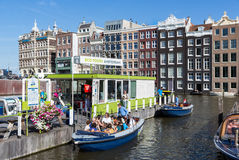 Motor boat with tourists at a departure place of Amsterdam canal cruises Stock Photo