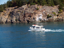 Motor boat tug on bay near rocky shore Stock Photography
