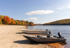 Motor boats on beach and fall colors Royalty Free Stock Images