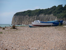 Motor boats at the coast. At the coast with boats, stones on the beach, details for bookcover, cliffs in the background, bushes, shrubberies and wood on the stock photo