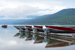 Motor boats line up in clear blue lake in Glacier. Stock Image