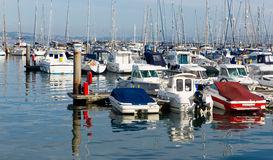 Motor boats in a marina with masts and calm blue sea. And reflections royalty free stock photo