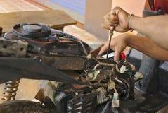 Motor car mechanic fixing motorcycle. Motor car mechanic fixing a broken motorcycle royalty free stock photos