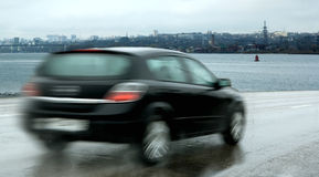 Motor car traveling at speed. Rear view of blurred motor car traveling at speed on highway with ocean and city shoreline in background Stock Photo