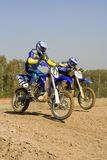 Motor challenge. Two motocross riders duelling on their motorcycles Royalty Free Stock Images