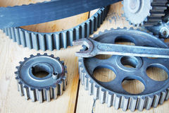 Motor cogwheels and a wrench lie on the wooden workbench Stock Photos