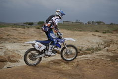 Motor cross cyclist off road. Side view of motor cross motorcyclist riding over rough terrain during Off Road Motorcycle race in Lesotho; 2008 Stock Image