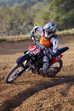 Motor Cross Racer. A motor cross racer leans into a dirt bank as he tries to maintain his first place lead Royalty Free Stock Photos