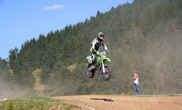 Motor cross rider in midair. Motor cross rider jumping midair on motor bike over course, European Championship competition, Zarnesti, Romania Royalty Free Stock Photography