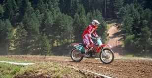 Motor cross rider on track. Motor cross rider on dirt track with forest in background, European Championship, Zarnesti, Romania Royalty Free Stock Images