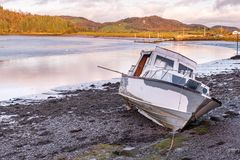 A motor cruiser boat lies on the mud waiting for the tide to return in Kippford, near Dalbeattie, in Dumfries and Galloway, Scotla stock image