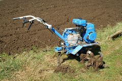 Motor-cultivator at the ploughed kitchen garden Royalty Free Stock Photo