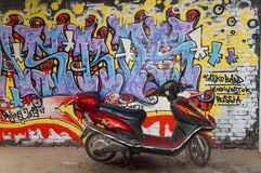 Motor cycle and art graffiti wall at 798 street,beijing. Art graffiti in Beijing Dashanzi Art District which houses an artistic community, among 50-year old Royalty Free Stock Photography