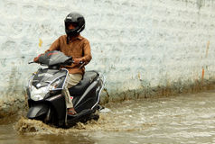 Motor Cyclist ride in rain water flooded road Stock Photography