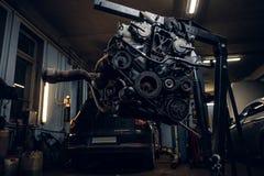 Motor de automóveis suspendido em uma grua hidráulica na oficina fotografia de stock