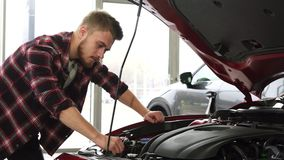Motor de examen del cutomer masculino hermoso de un coche en la sala de exposición de la representación almacen de video