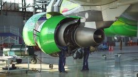 Motor en chassis van het passagiersvliegtuig onder zwaar onderhoud De ingenieur controleert de vliegtuigenmotor stock videobeelden