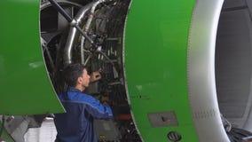 Motor en chassis van het passagiersvliegtuig onder zwaar onderhoud De ingenieur controleert de vliegtuigenmotor stock footage