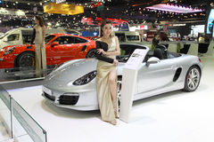 Motor expo. A pretty women is posing near car brand Porsche Stock Image