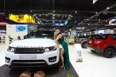 Motor expo. A pretty women is posing near car brand Range Rover royalty free stock photos