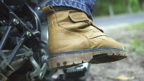 Motor för motorcykliststartmotorcykel vid kickstarter Slut upp motocyklistbenet som startar motorcykeln för körning stock video