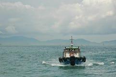 Motor ferry yacht sailing away in Hong Kong bay Royalty Free Stock Photo