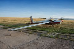 Motor glider. On the green runway at sunset Royalty Free Stock Image