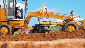 Motor grader leveling ground. Construction site machinery