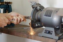 Motor Grinder. A worker grinding metal rod with sparks flying Stock Image