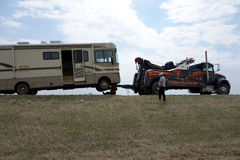 A motor-home being lifted by a tow truck. A recreational vehicle broken down by the side of a highway in canada Royalty Free Stock Images
