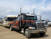 A motor home being towed in canada. A large RV being backed into a repair yard by a heavy-duty towtruck Stock Image